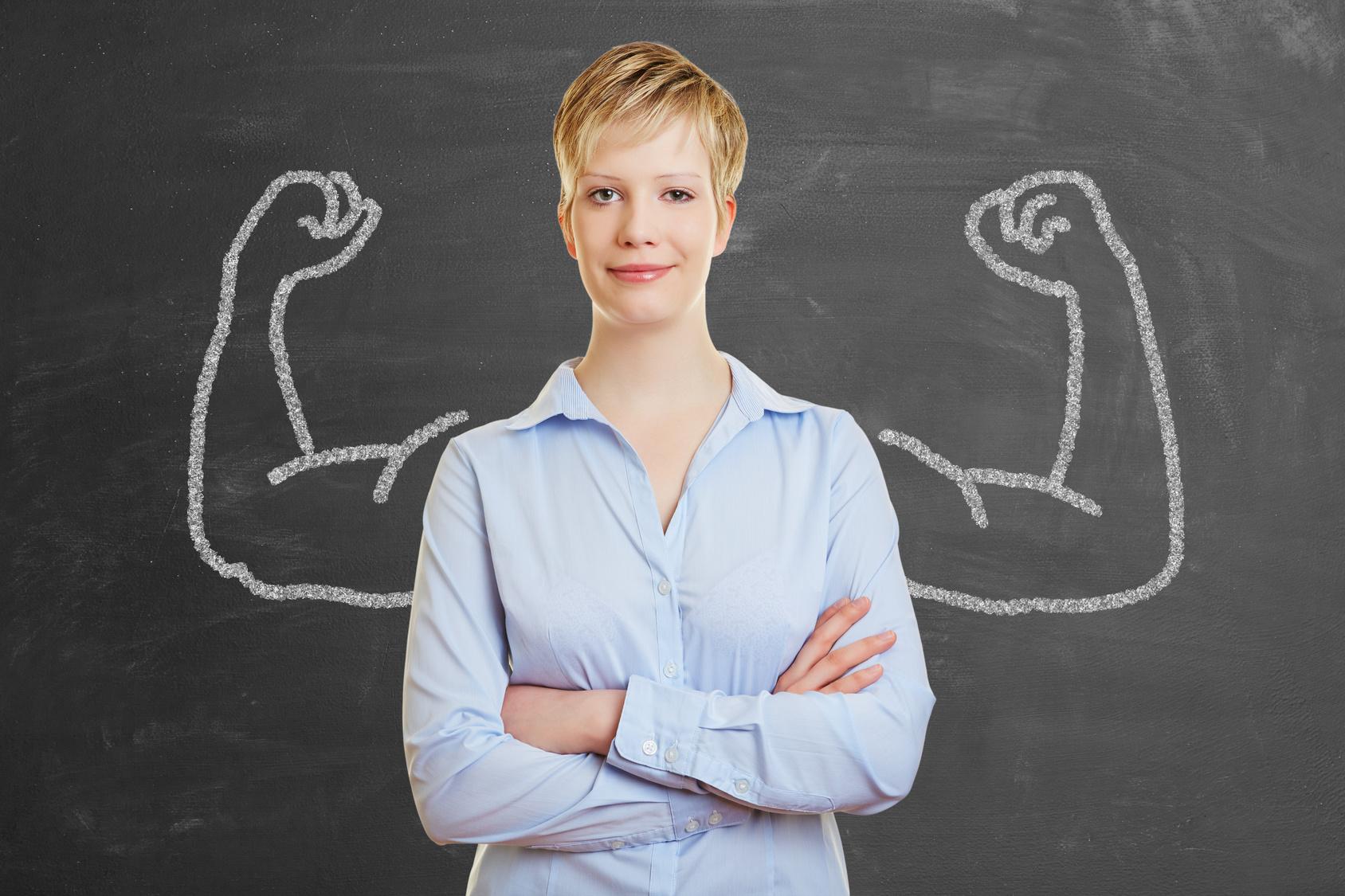 Starke Frau vor Tafel mit Muskeln