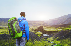 hiker with backpack enjoying beautiful panoramic view of mountains in Iceland, volcanic landscape, travel background